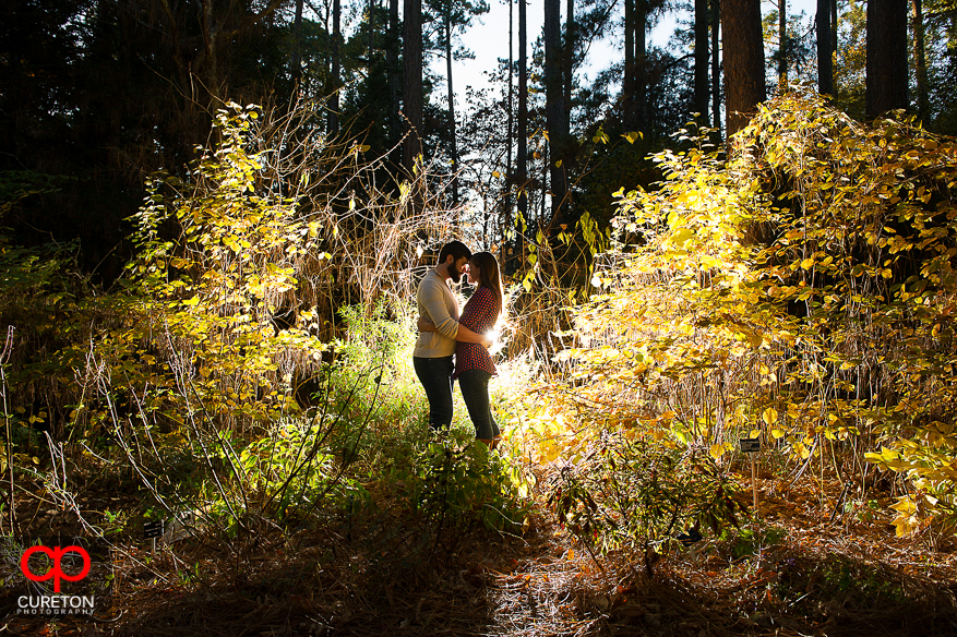 A Couple In Some Bushes During Their Botanical Gardens Engagement Session  In Clemson,SC.