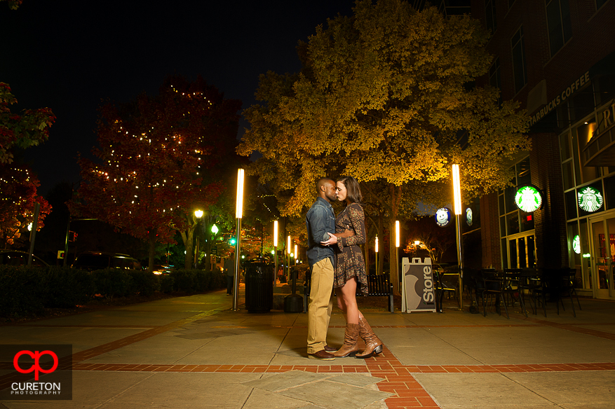 Couple kissing on Main St. during their downtown Greenville,SC engagement session.
