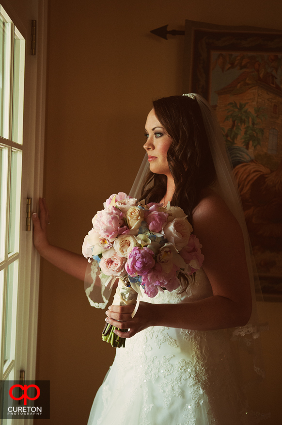 The bride staring out the window before hew wedding.