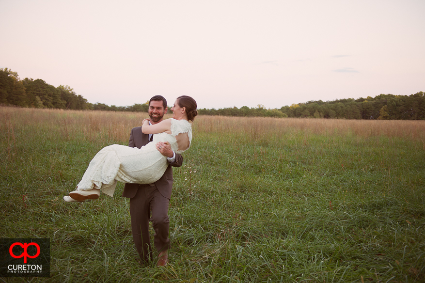 Groom carries bride in the field at Lenora's Legacy.