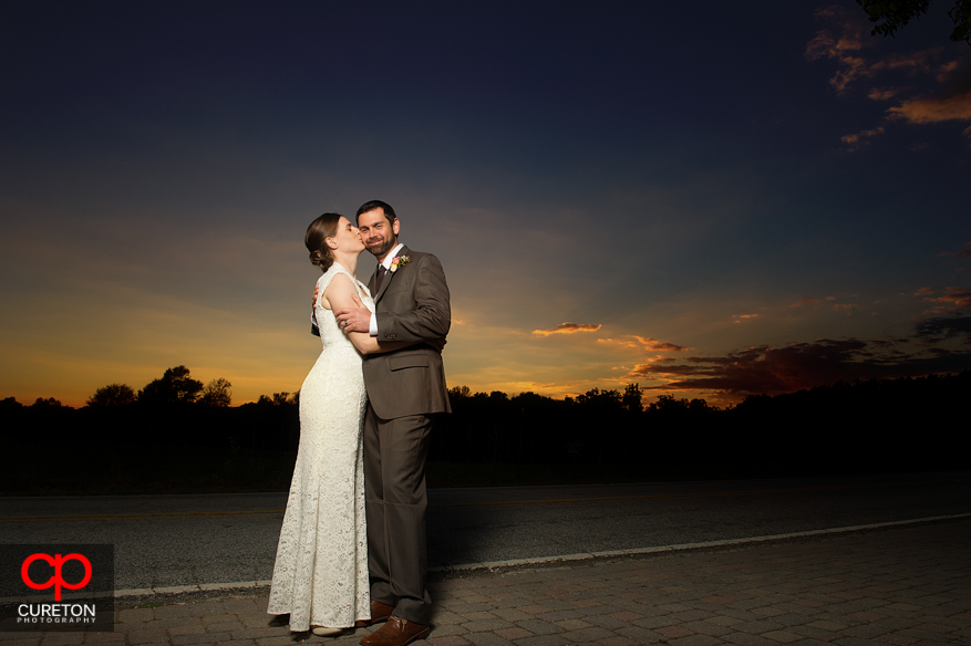 Bride kissing groom at sunset.