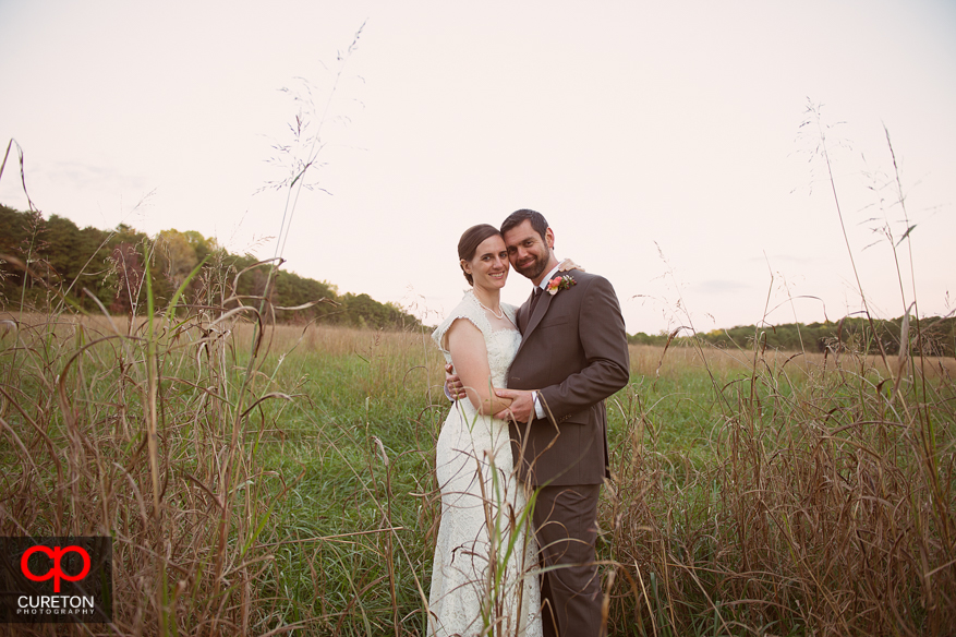 Bride and groom pose in a field.