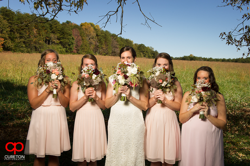 Bridesmaids with flowers covering their faces.