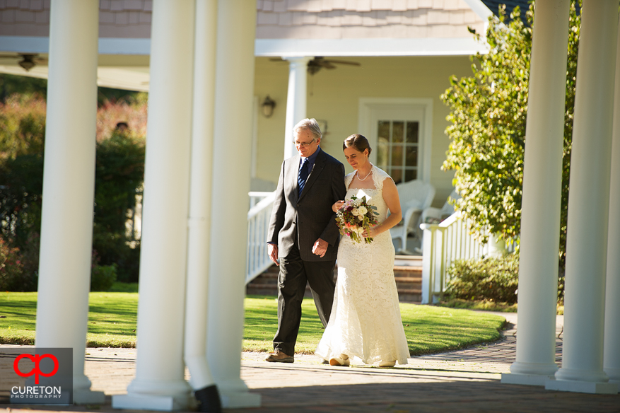 Bride and father walk down the aisle.