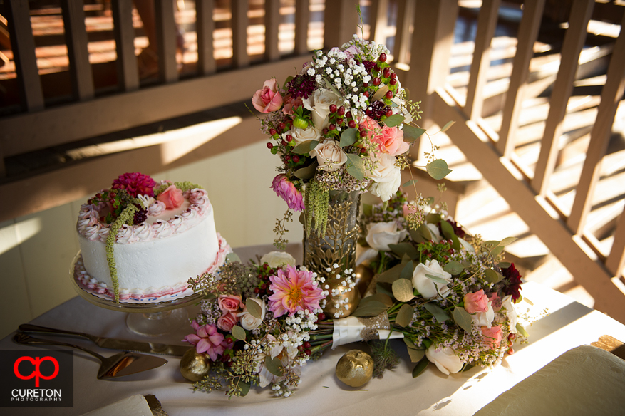 Awesome floral arrangement next to the wedding cake.