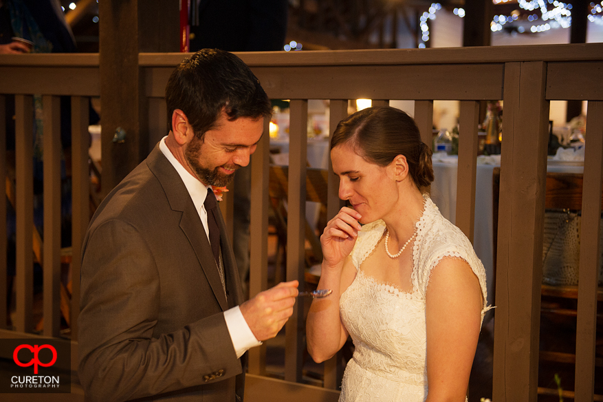Groom feeds bride cake.