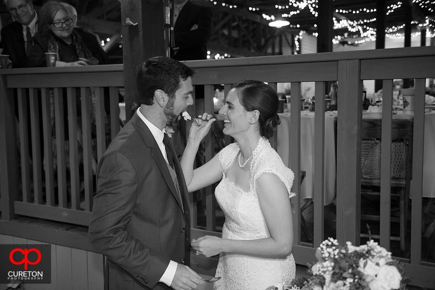 Bride feeds groom cake.