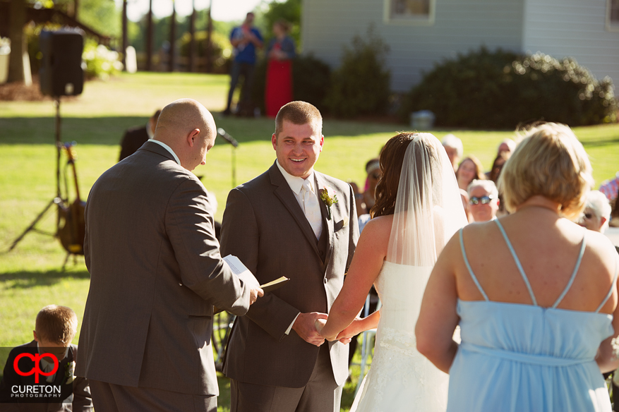 The groom smiling during the ceremony.