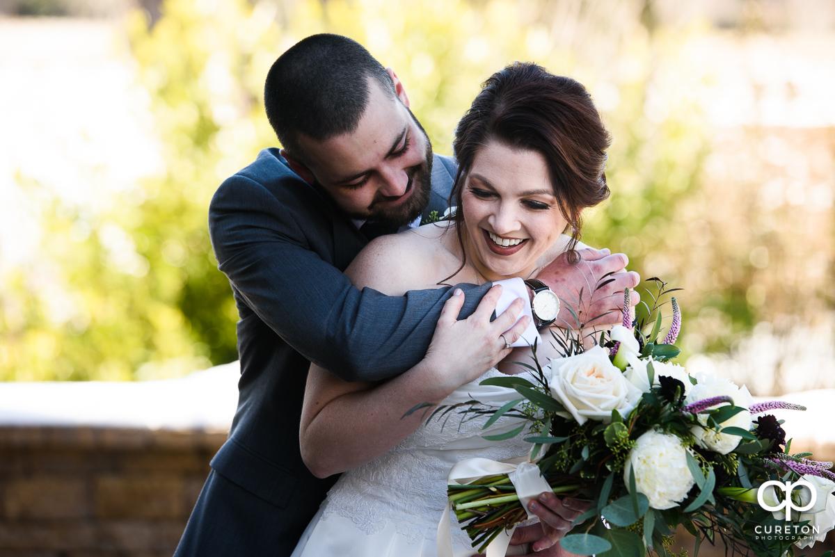 Groom hugging his bride before the wedding.