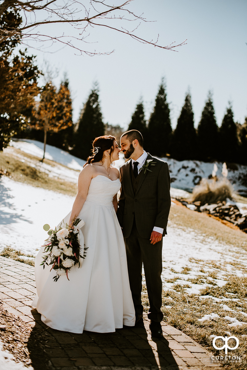 Brode and Groom in the playing in the snow after their wedding ceremony at The Arbors in Cleveland,NC.