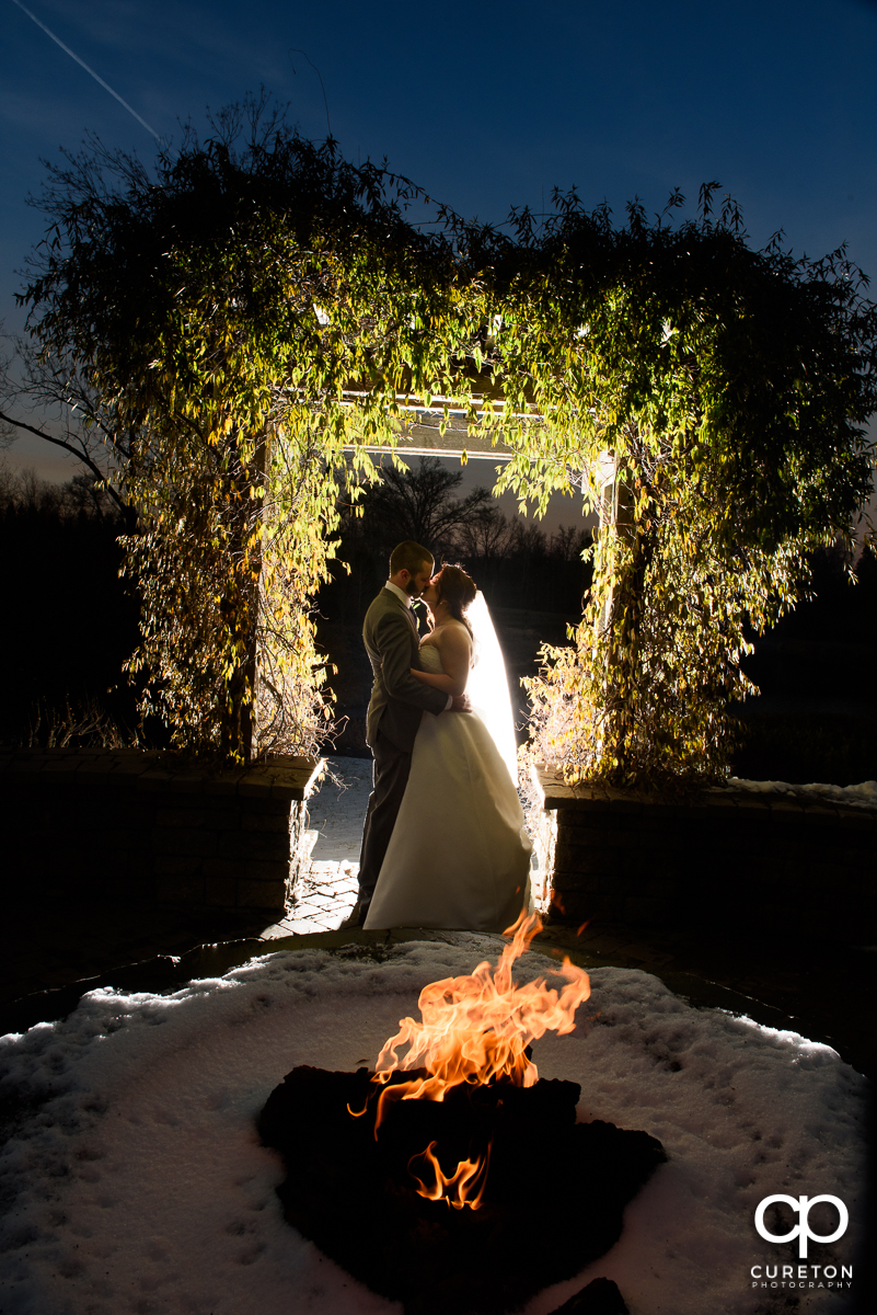 Brode and groom kissing by the fire pit after their wedding at The Arbors in Cleveland,NC.