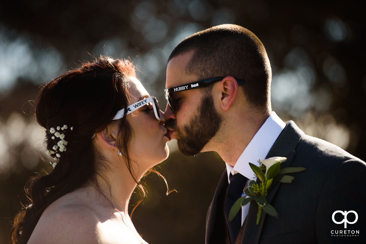 Bride and groom kissing while wearing printed sunglasses with the words wifey and hubby on them.