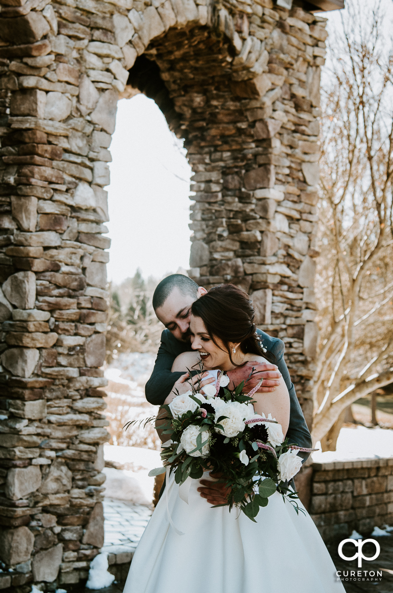 Groom hugging his bride in the snow after their wedding at The Arbors in Cleveland,NC.