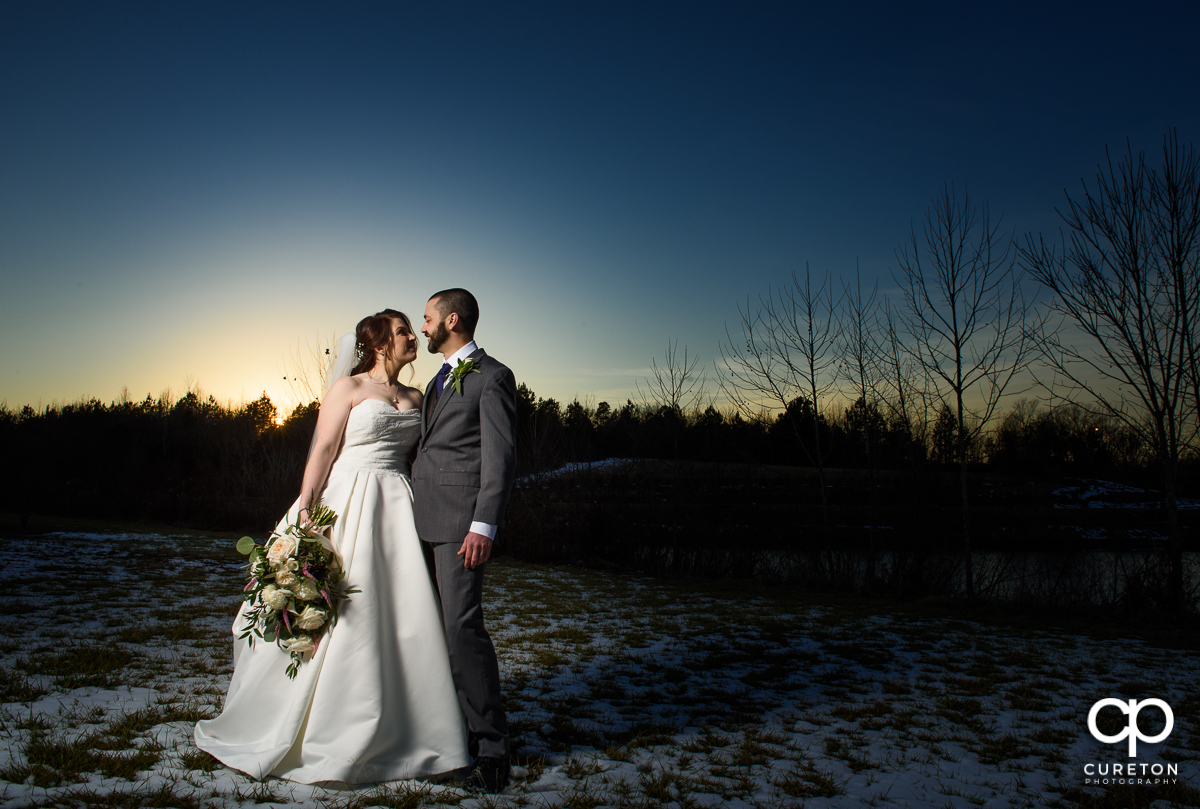 Bride and groom in the snow at sunset after their wedding near Lake Norman.