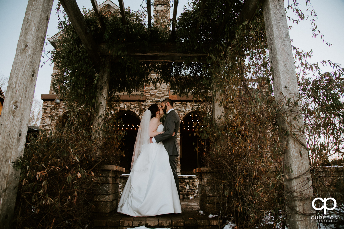 Bride and groom under a pergola at their wedding at The Arbors in Cleveland NC.
