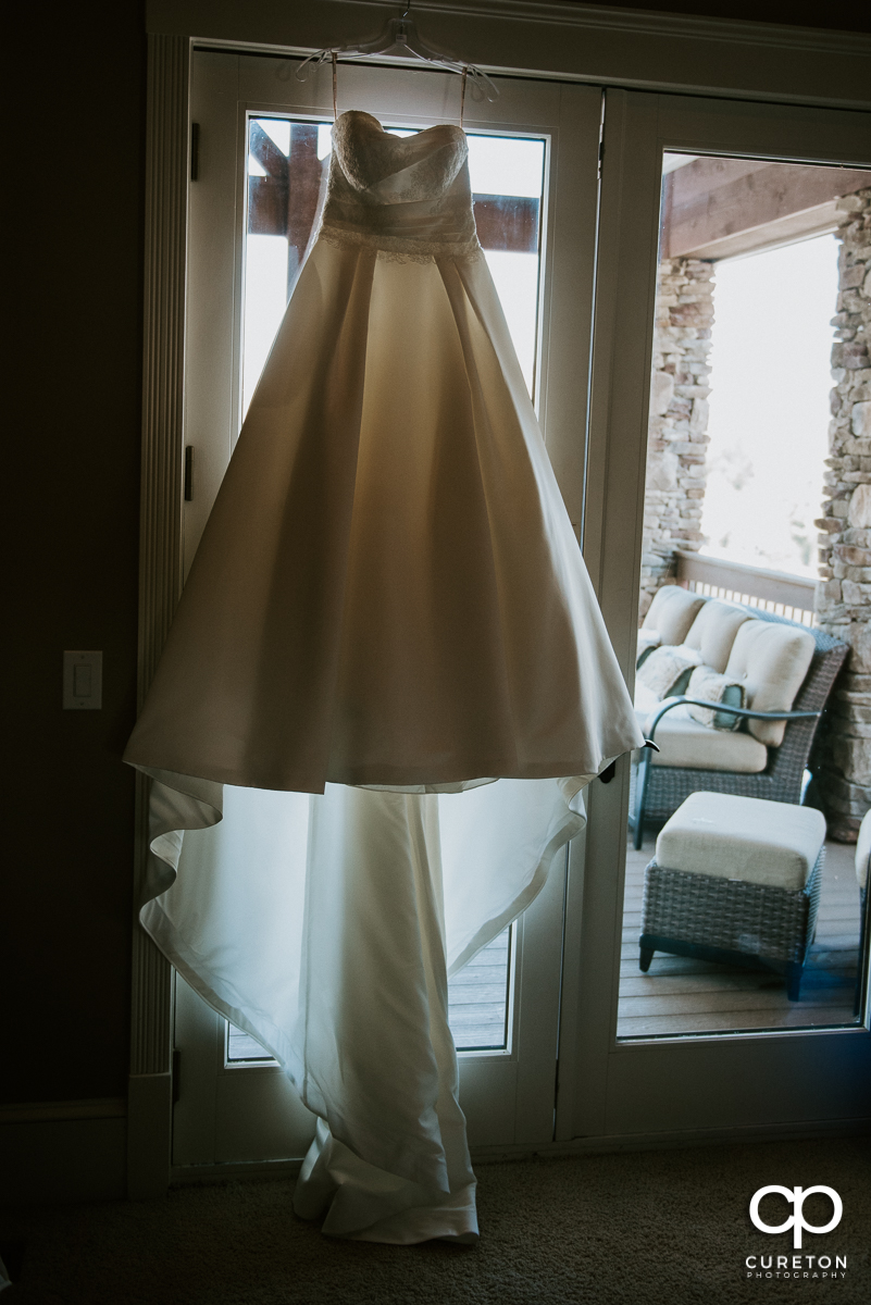 Bride's dress hanging up in a window.