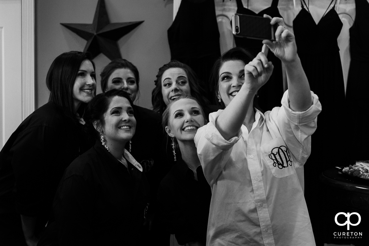 Bride taking a selfie with her bridesmaids.