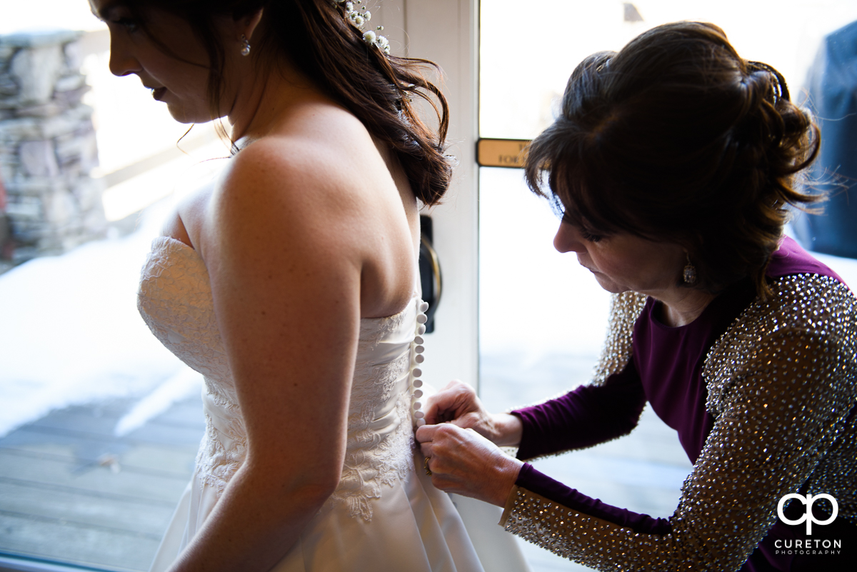 Bride's mother buttoning the back of her dress.