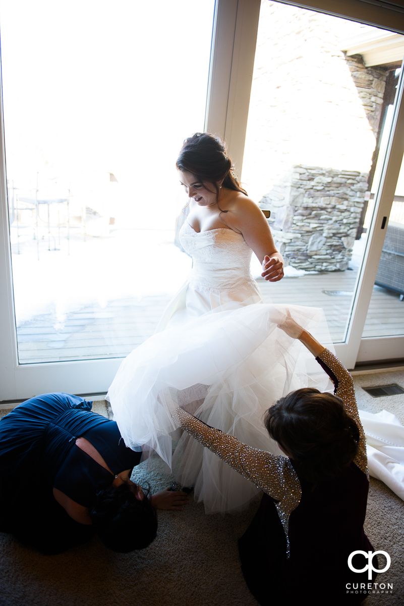 Bride getting helped into her dress.
