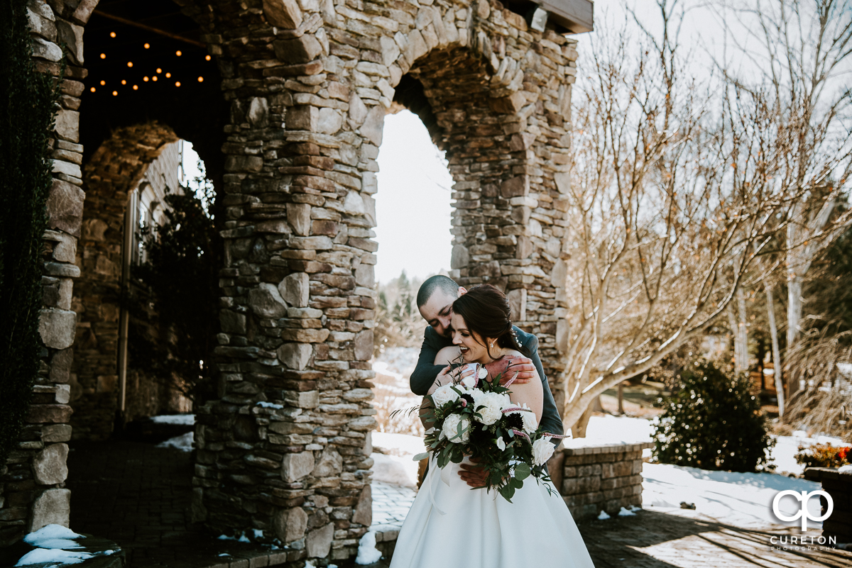 Bride and groom cuddling in the snow before their Cleveland NC wedding at The Arbors.