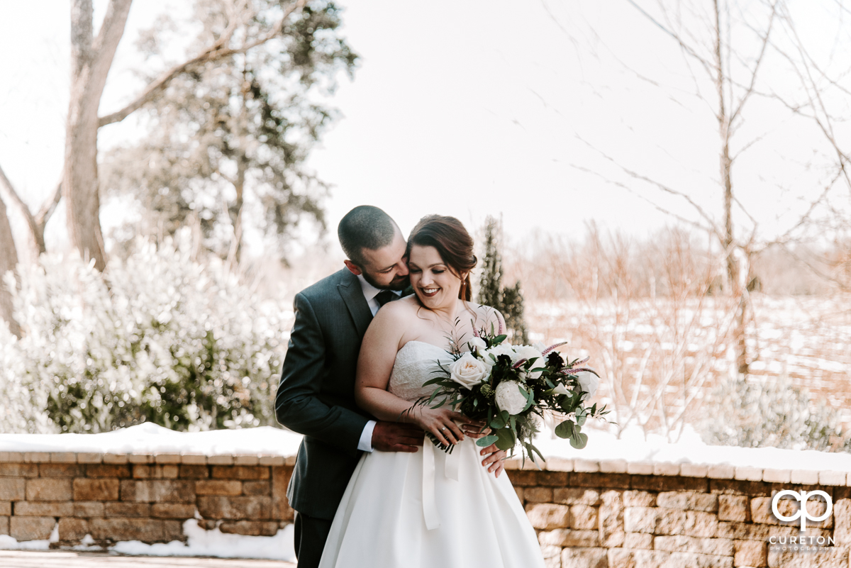 Bride and groom getting close in the snow before their wedding near Lake Norman.