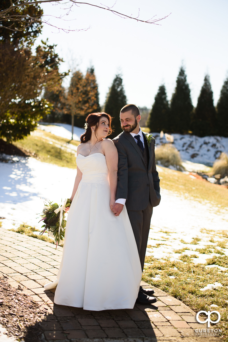 Bride and groom playing in the snow before their wedding.