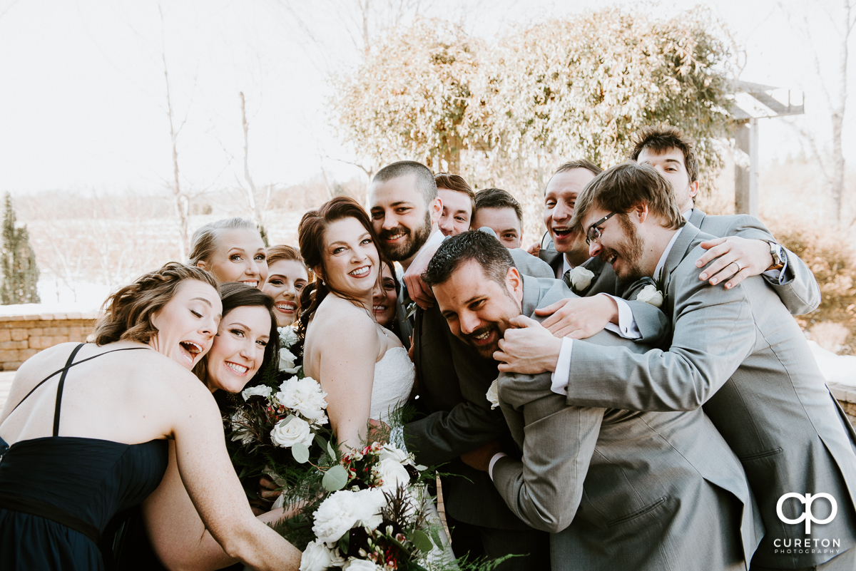 Wedding party hugging the bride and groom at once.