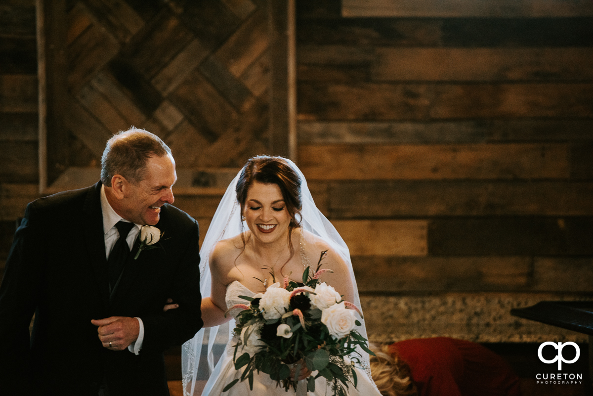 Bride and her father laughing while walking down the aisle at the wedding ceremony.