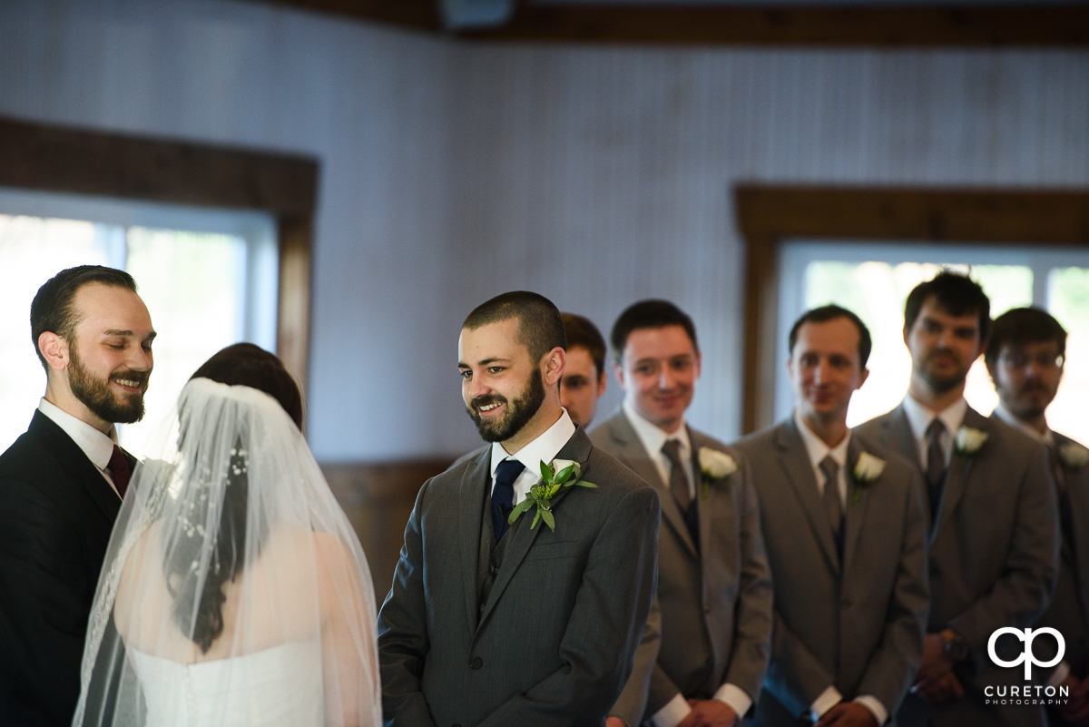Groom smiling at the bride during the ceremony.