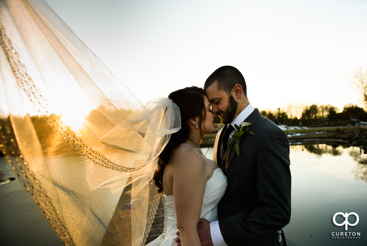 Newlyweds by the lake with the bride's veil blowing in the wind.