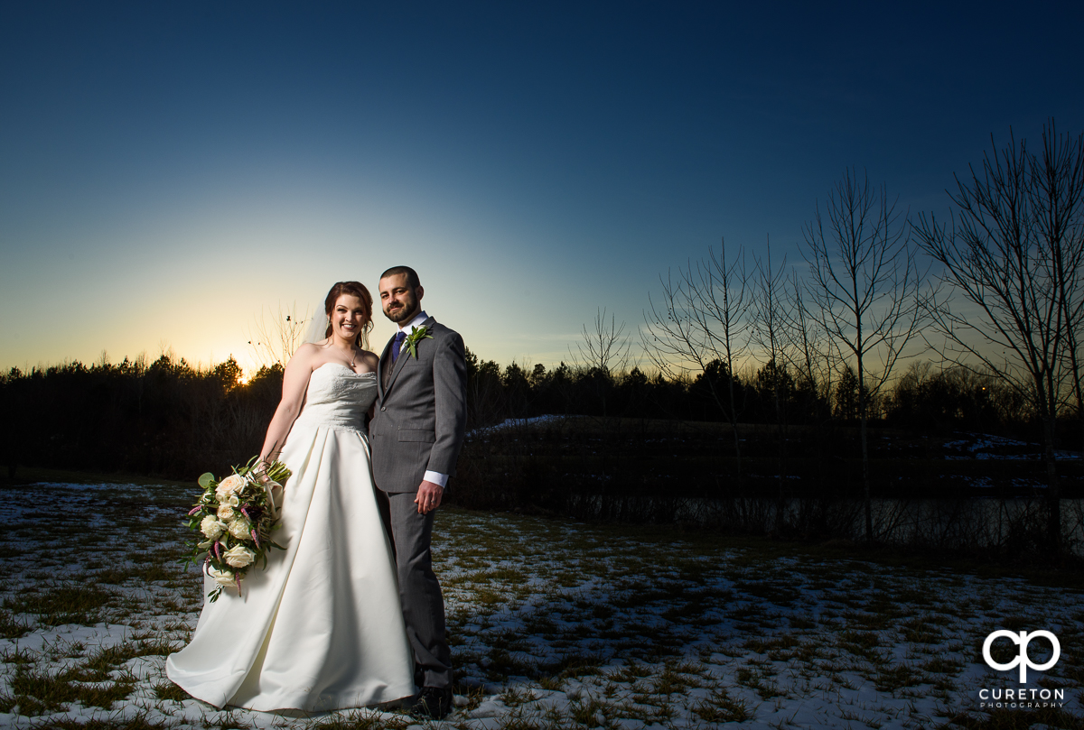Bride and groom at sunset standing in the snow.