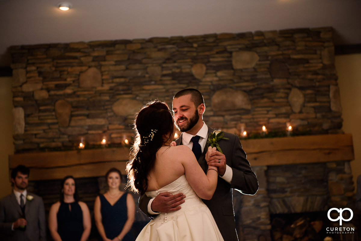 Groom smiling during the first dance with his bride.