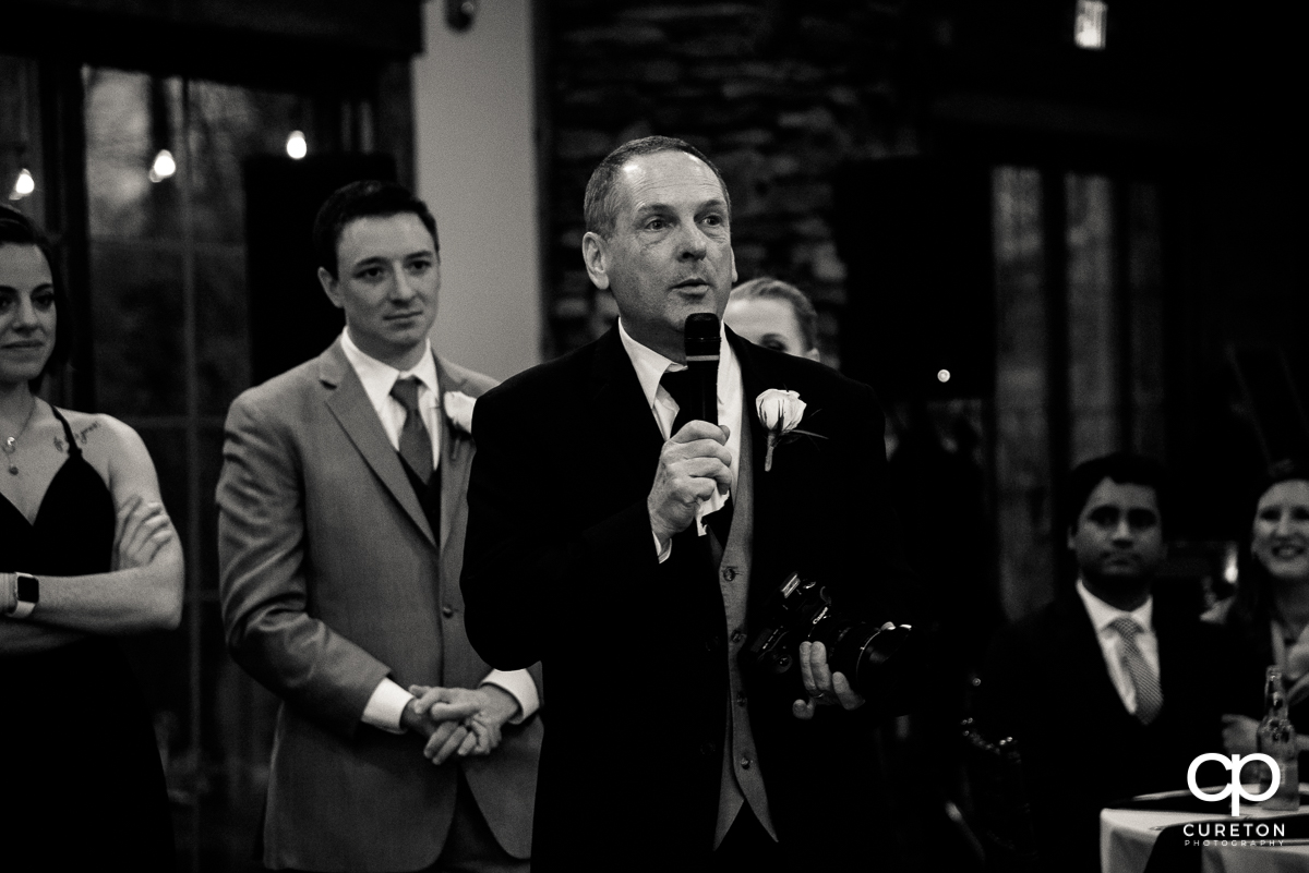 Bride's father holding the microphone.