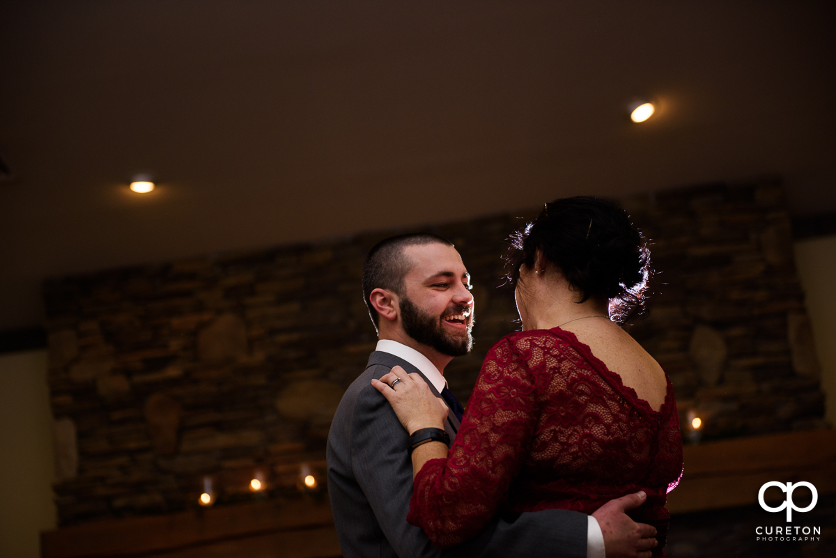 Groom smiling during a dance with his mother.
