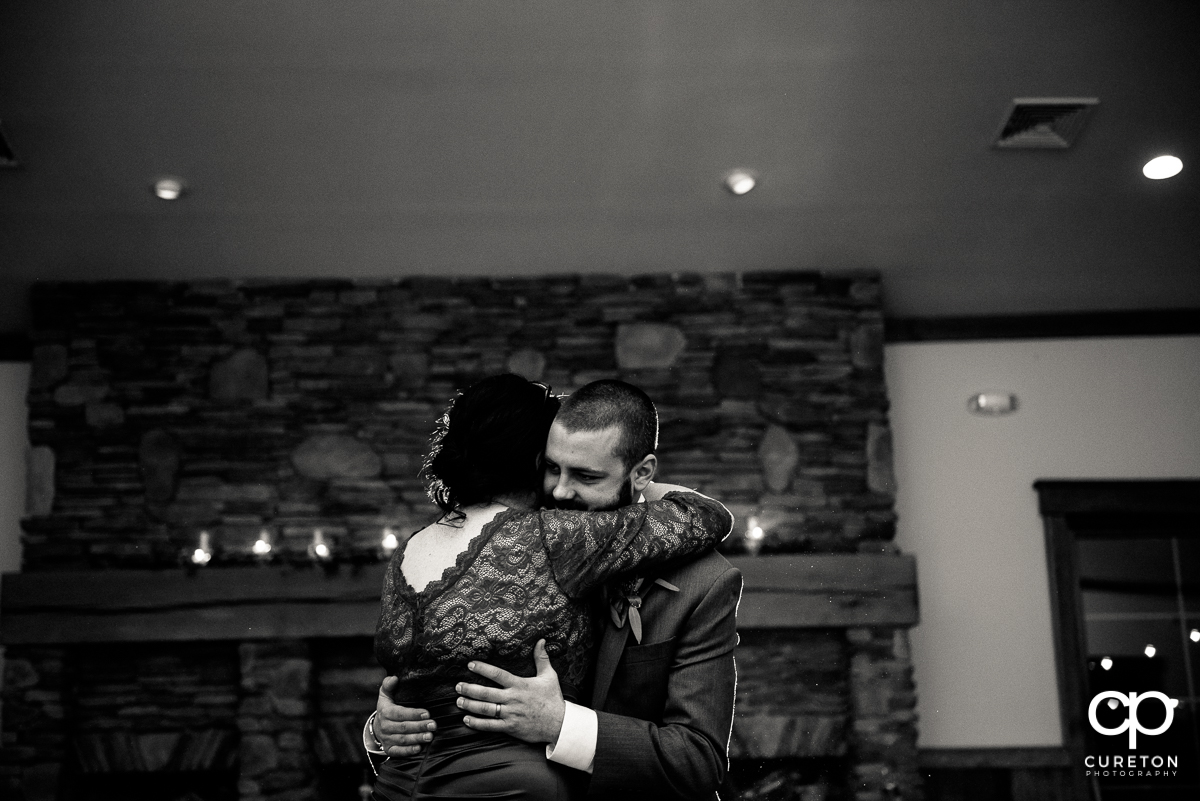 Groom getting a hug from his mom at the reception.