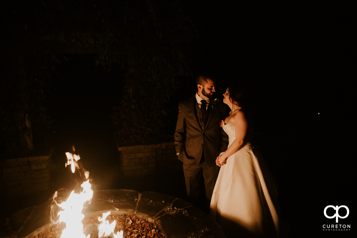 Bride and groom lit by the firepit at The Arbors in Cleveland,NC wedding reception.