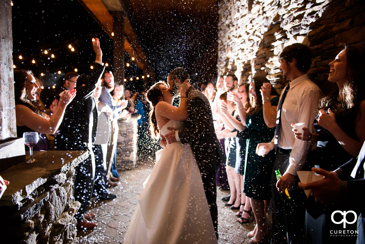 Married couple making a grand exit as the guests throw fake snow.