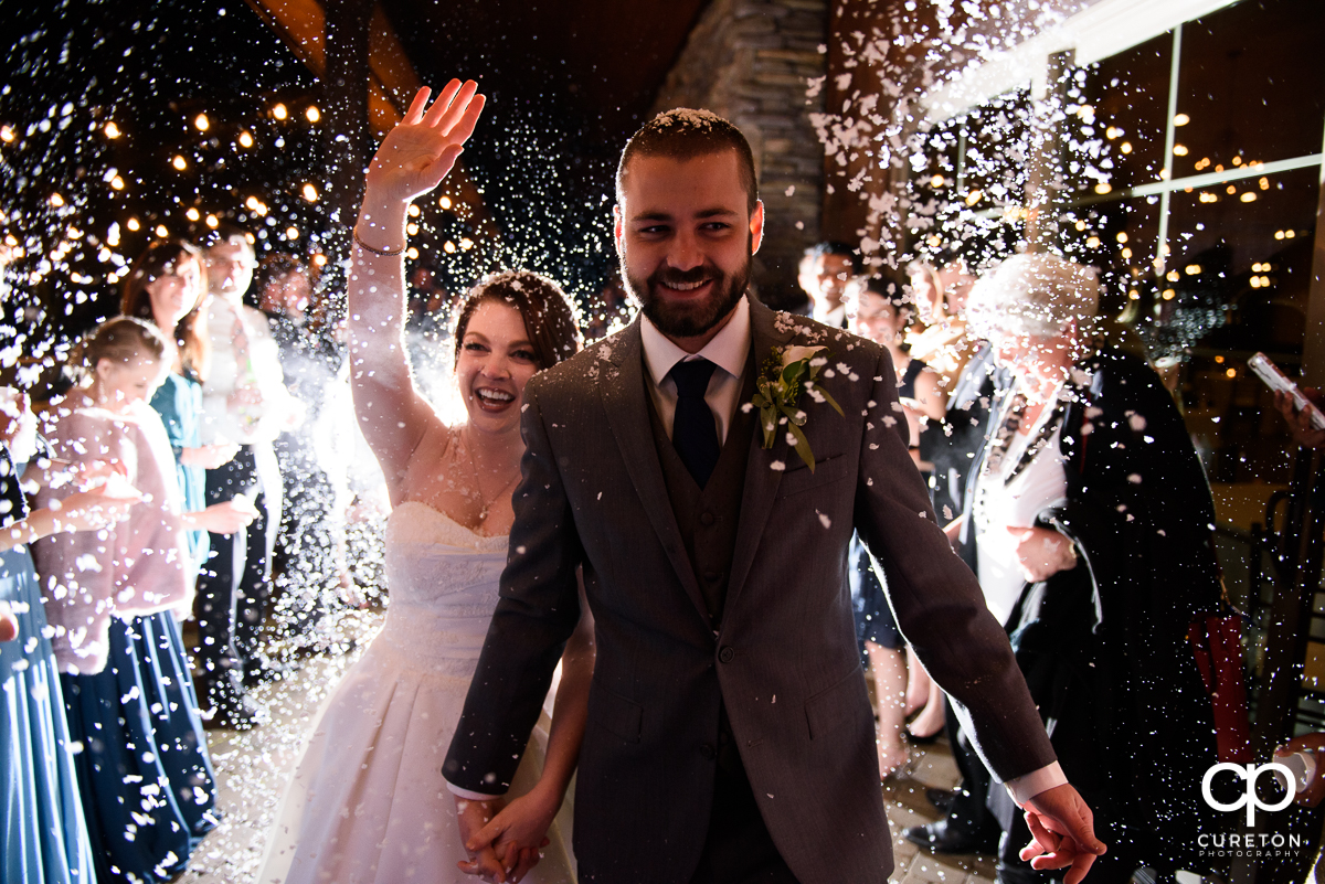 Married couple making a grand exit as the guests throw fake snow at the reception.