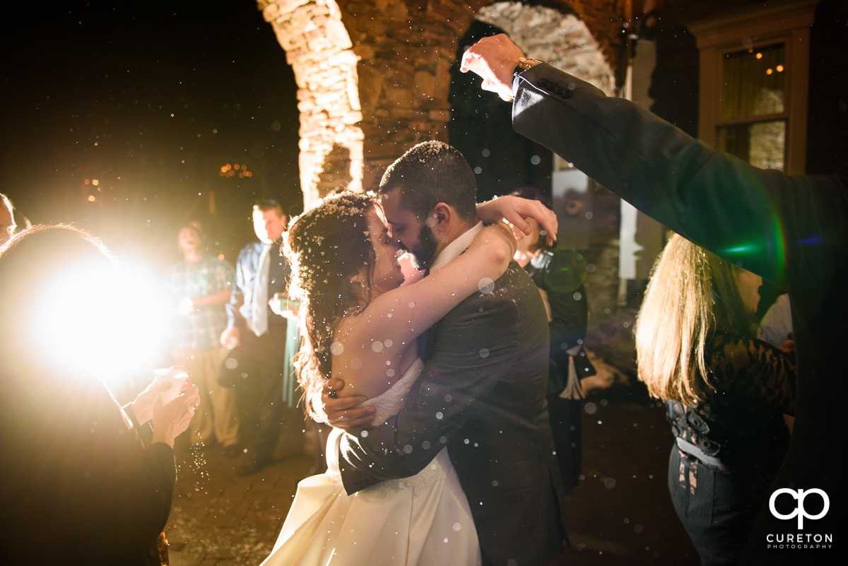 Bride and groom making a grand exit as the guests throw fake snow.