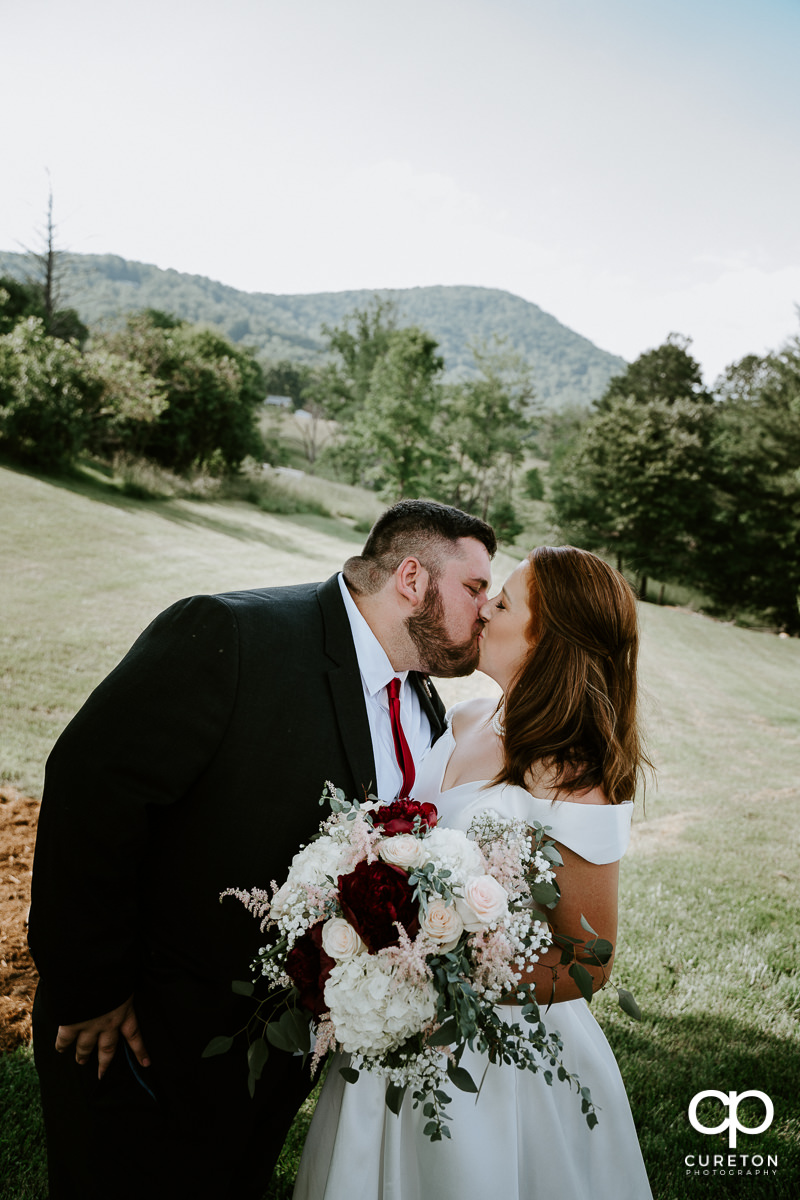 Bride and groom kissing underneath a tree after their Asheville NC outdoor wedding.