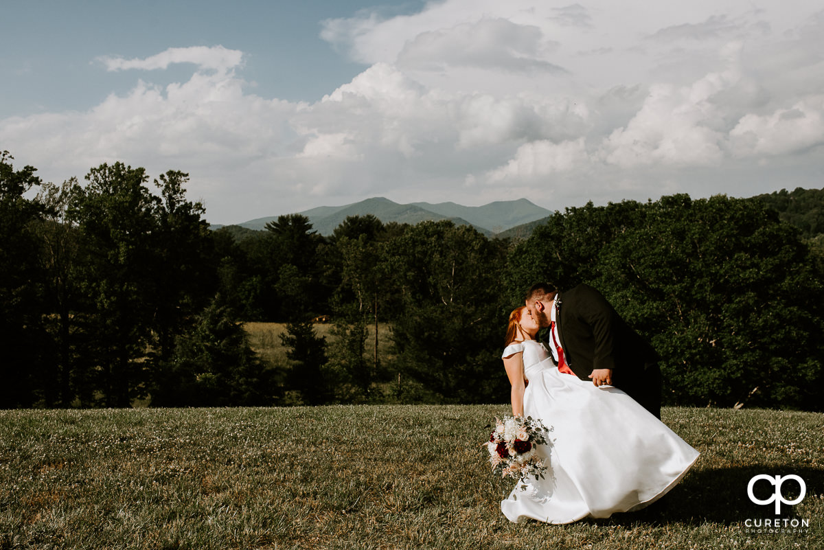 Groom dipping his bride in front of a mountain overlook after their Asheville NC outdoor wedding..