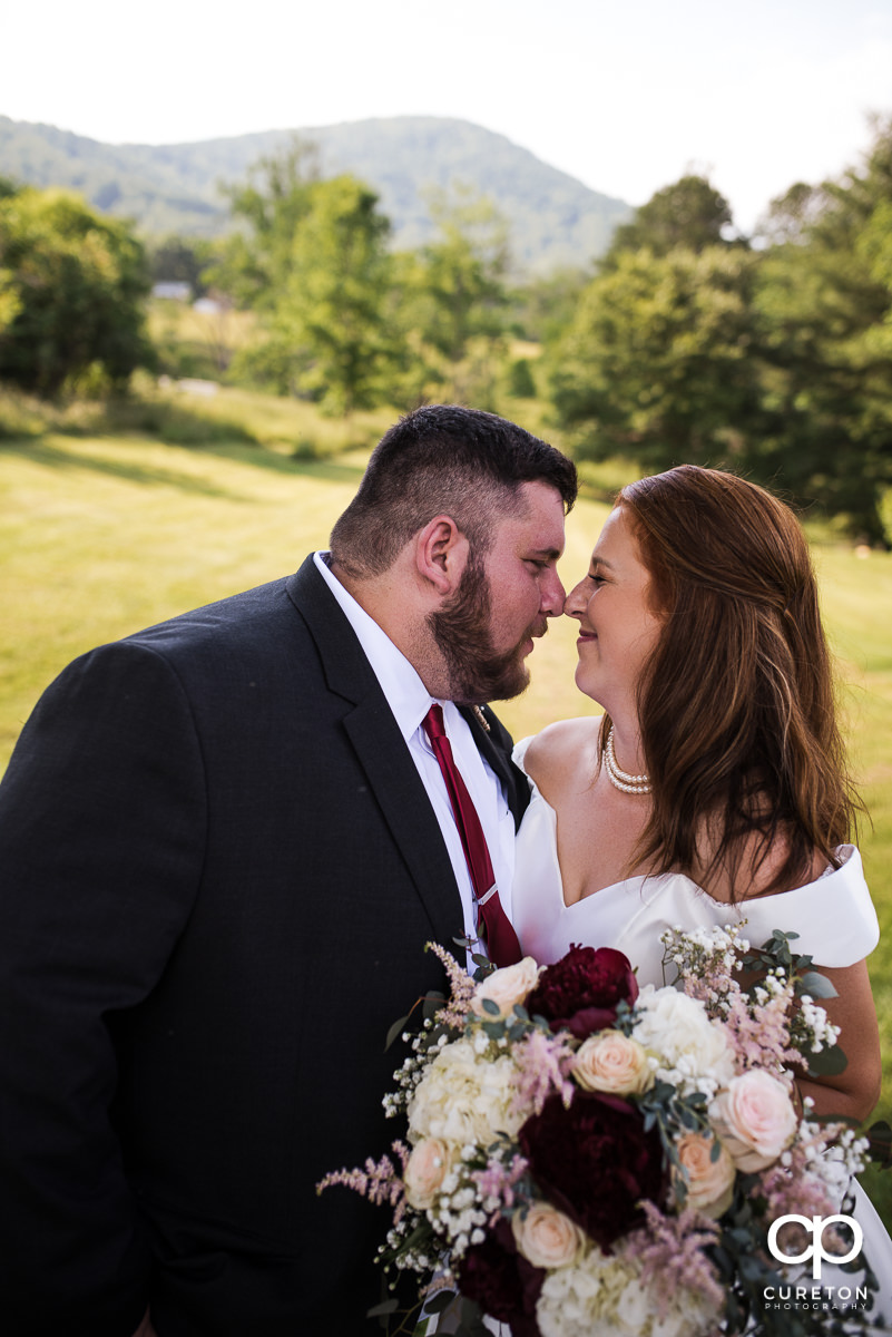 Groom and bride eskimo kissing each other after their Asheville NC outdoor wedding.