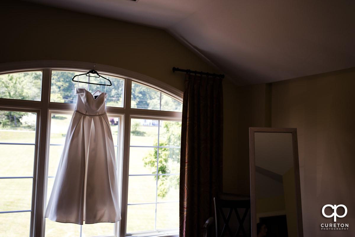 Bride's dress hanging in a window.