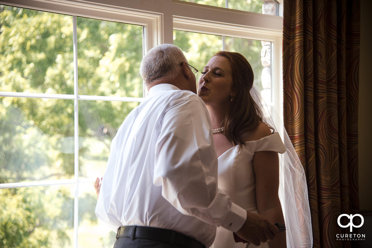 Bride kissing her dad on the cheek.
