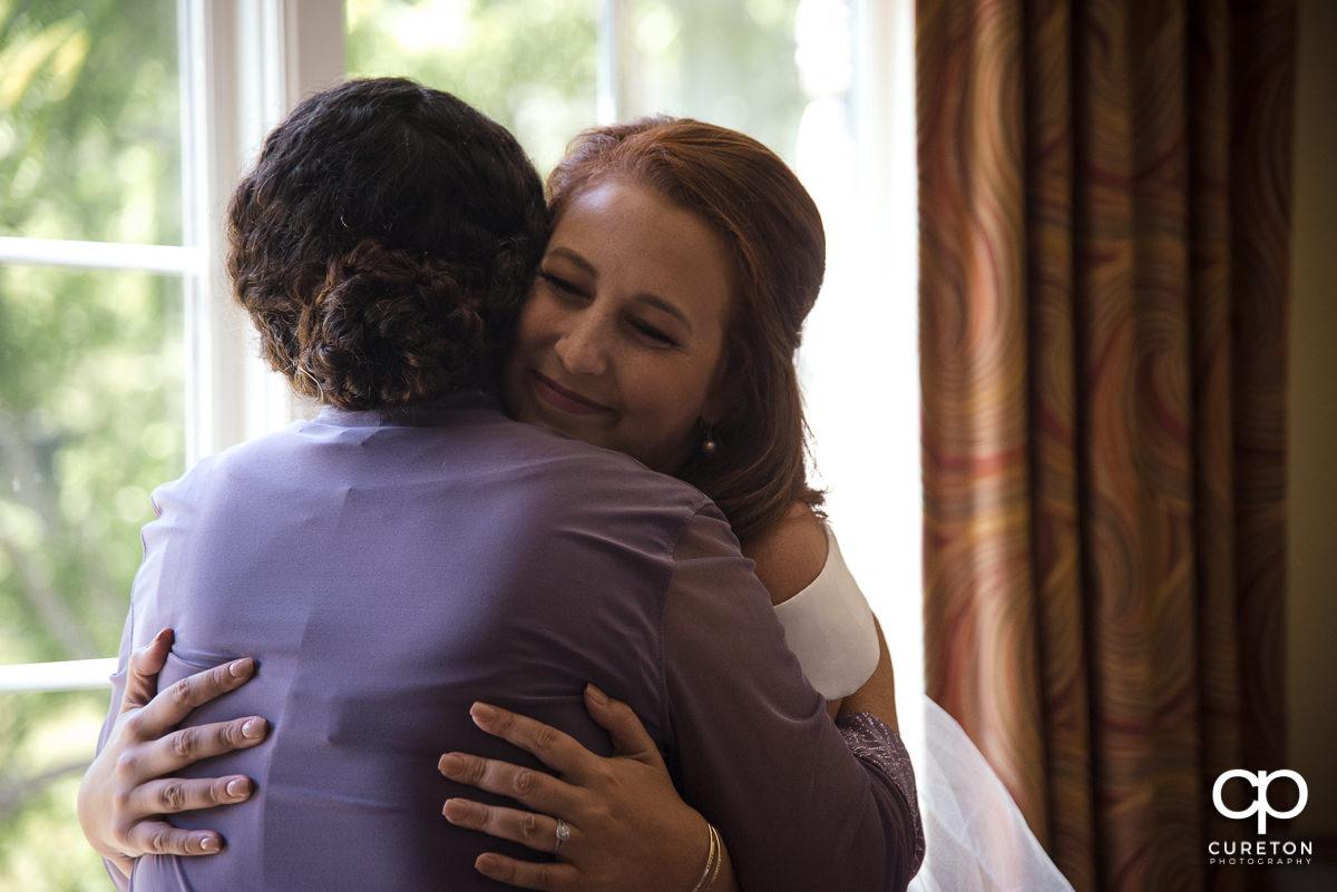 Bride hugging her mom.