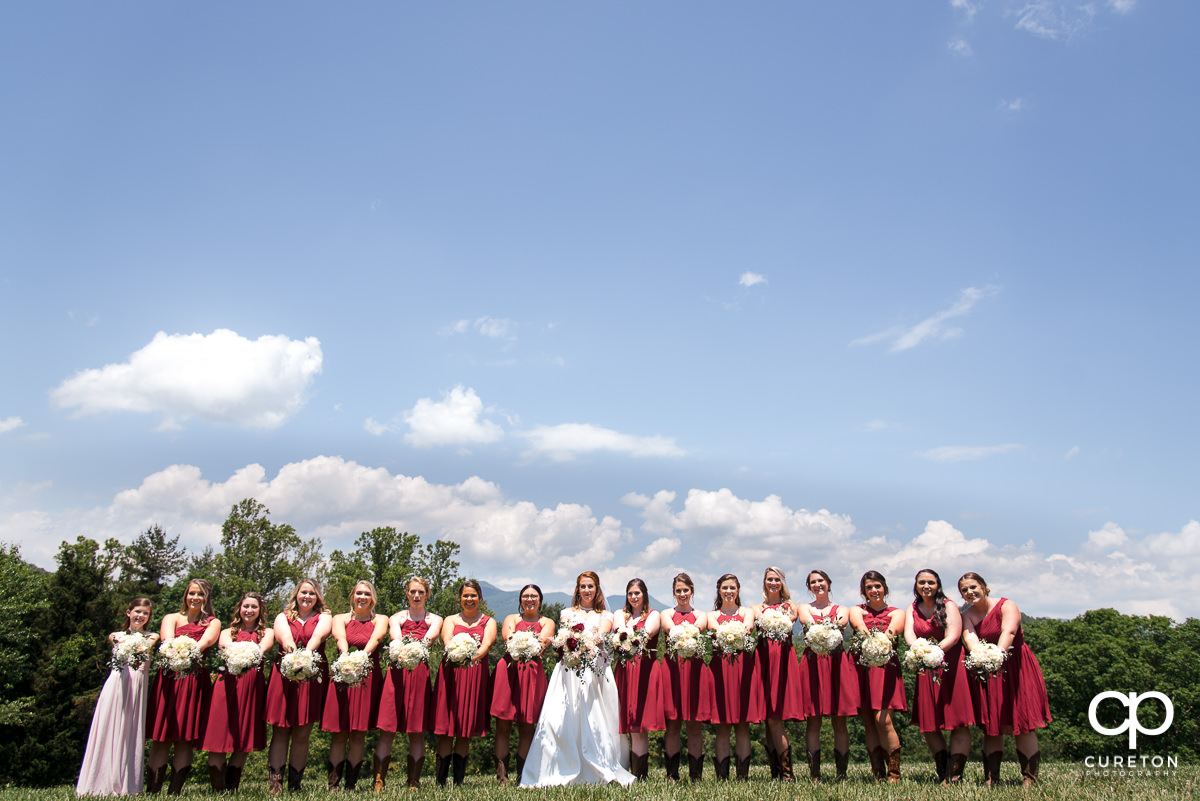 Bridesmaids holding their flowers in a field before their Asheville NC outdoor wedding.