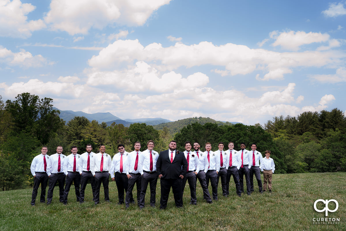 Groom and groomsmen in front of a mountain overlook in a field in Asheville,NC.