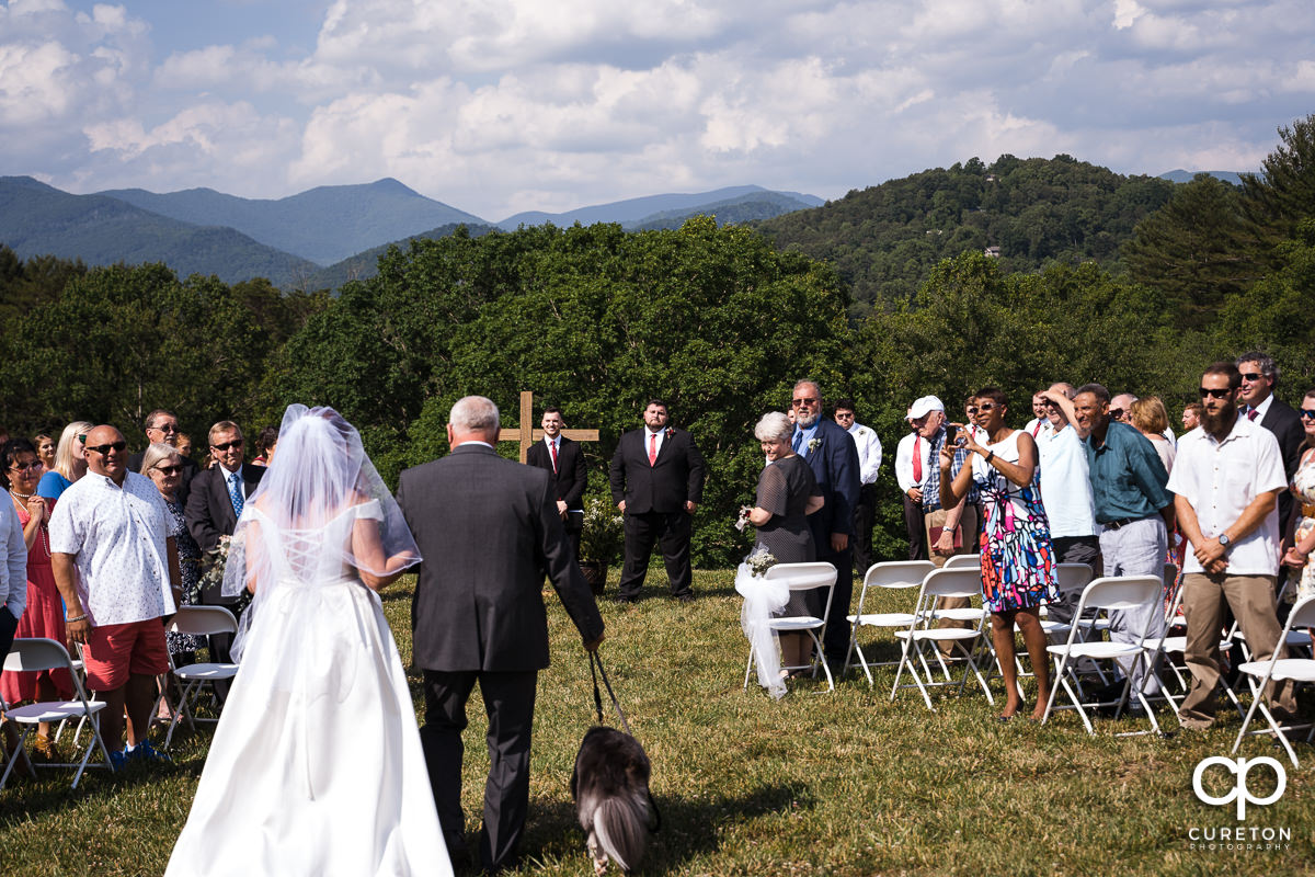 Bride, her father, and her dog walking down the aisle towards her groom.