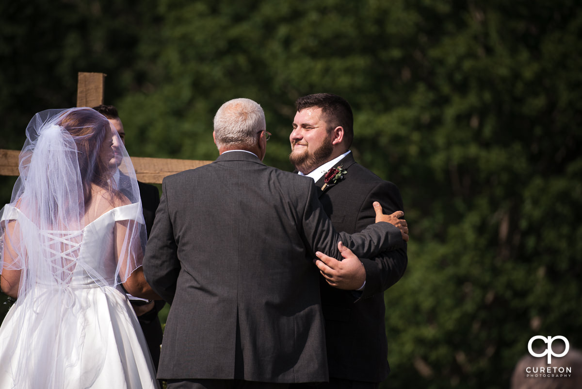 Groom smiling at his father in law.