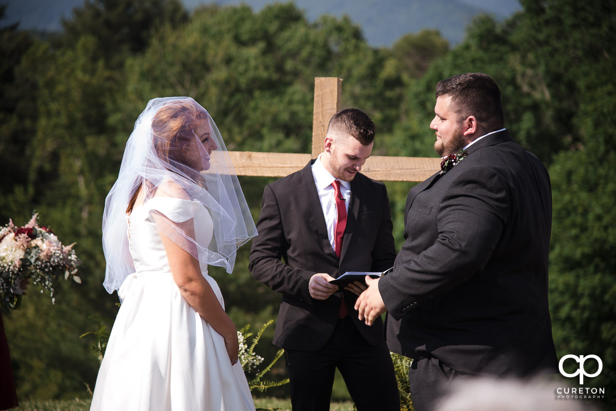 Bride and groom facing each other during the outdoor wedding ceremony in Asheville ,NC.